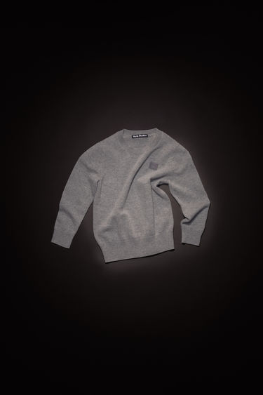 Acne Studios children's grey melange crew neck sweater is made from wool with a face logo patch and ribbed details.