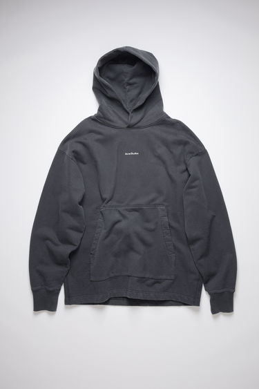 Acne Studios black hooded sweatshirt is crafted from organically grown cotton that's garment dyed for a soft, washed out finish. It's cut for an oversized fit that drapes loosely over the frame and features a raised logo print on front.