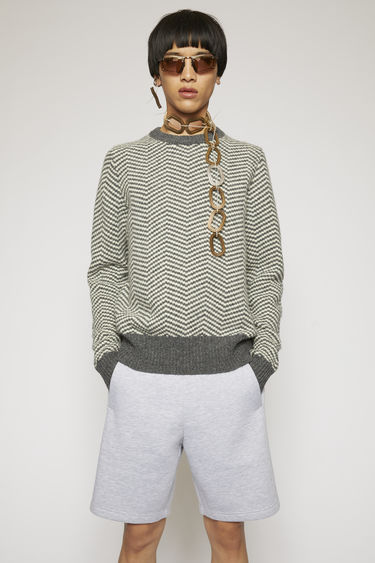 Acne Studios white/grey sweater is knitted from Shetland wool in chevron intarsia design and completed with ribbed crew neck, cuffs and hem.