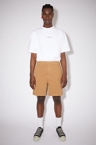 Acne Studios camel brown loose-fitting shorts are made of a cotton twill with a slight stretch.