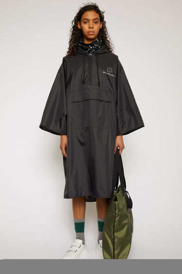 Acne Studios black poncho is crafted from technical shell fabric to an oversized silhouette with a drawstring hood and front patch pocket and features a reflective logo-print across the chest.