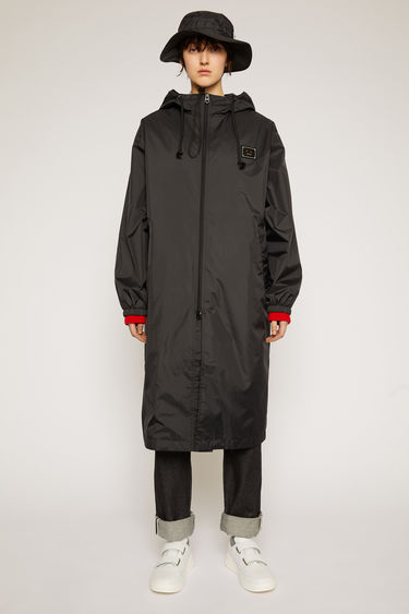 Acne Studios black raincoat is crafted from technical shell lined with mesh and features a drawstring hood and two-way zip closure and a metal face-motif plaque on the chest.
