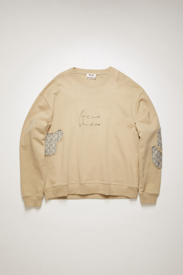 Acne Studios cold beige sweatshirt is cut to an oversized fit and mended with jacquard patches to enhance a well-worn look. It shaped with a ribbed crew neck and features a handwritten logo embroidered across the chest.