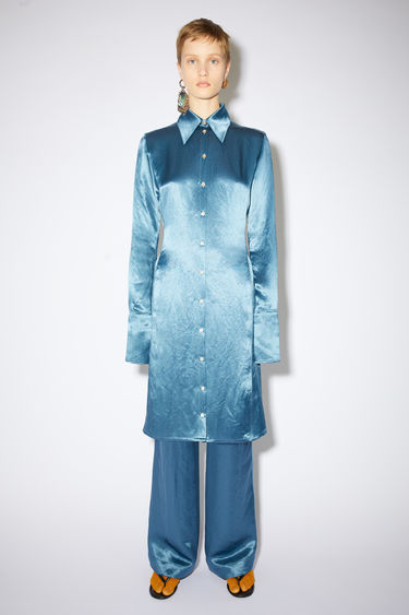Acne Studios dusty blue long sleeve shirt dress is made of fluid satin with a fitted silhouette.