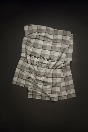 Acne Studios grey/black scarf is crafted from wool that's twill-woven in a classic shepherd's check pattern and emblazoned with a large-scale printed logo and care instruction.