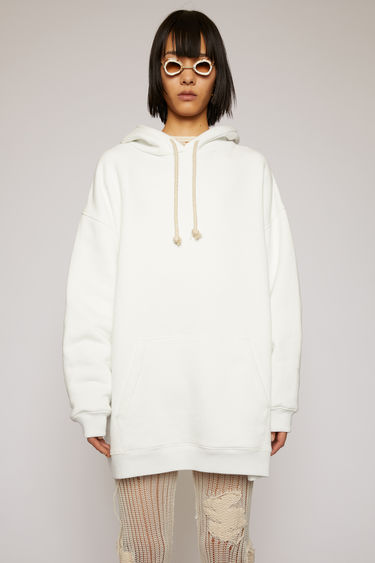 Acne Studios optic white hooded sweatshirt is crafted for an oversized fit from midweight loopback jersey and adorned with a label patch that's left with loose thread for a subtle note of texture.