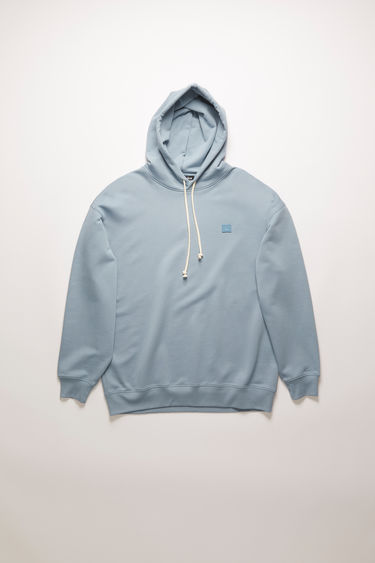 Acne Studios mineral blue hooded sweatshirt is crafted from midweight loopback jersey to an oversized fit and accented with a tonal face-embroidered patch on the chest.
