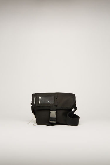 Acne Studios black messenger bag is crafted to a boxy shape with raw-edged trim and features an adjustable shoulder strap and a transparent card pocket on the flap.
