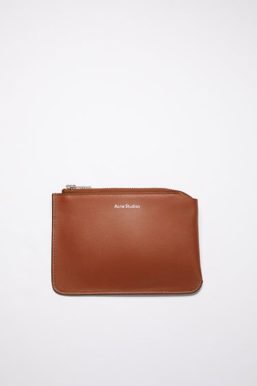 Acne Studios almond brown zip wallet is crafted from soft grained leather with a silver stamped logo and features a metal zip fastening that opens to reveal a leather-lined interior to store your notes, cards and coins.