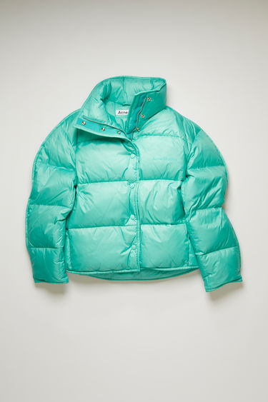 Acne Studios turquoise blue down jacket is padded with recycled down and feathers and is shaped to a cocoon silhouette with binding running along the edges. The funnel collar has a packaway hood and accented with a tonal logo print at the chest.