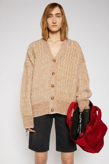 Acne Studios camel/white melange cardigan is knitted in a wavy variation of the traditional ribbed pattern then brushed to a soft handle. It's shaped to an oversized silhouette with dropped shoulders and finished with thick ribbed edges at the V-neck, cuffs, and hem.