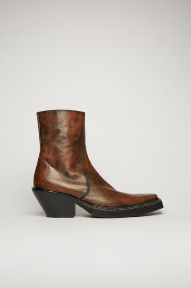 Acne Studios brown western ankle boots are crafted from grained leather and feature an elongated point toe and a fitted shaft. It's set on a slanted block heel and finished a metal zip fastening on the side.