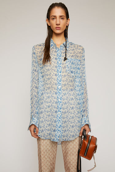 Acne Studios blue/white blouse is crafted from crinkled silk chiffon and patterned with a floral print reminiscent of vintage wallpapers. It's cut to a relaxed fit with a point collar and an asymmetric shirttail hem.