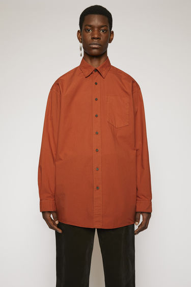 Acne Studios brick red oversized shirt is crafted from pure cotton that's garment dyed for softness and then finished with a patch pocket on the chest.