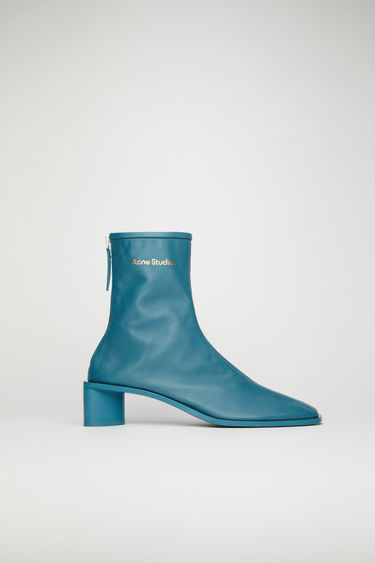 Acne Studios teal blue/teal blue boots are crafted from soft grained leather to a snug sock-like fit and set on a tonal block heel. They're secured with a metal zip and accented gold stamped logo on the ankle.