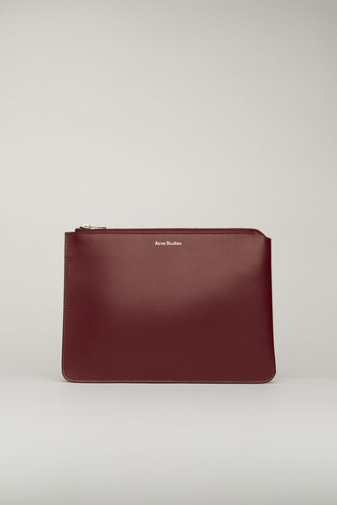 Acne Studios burgundy document holder is crafted from soft grained leather with a silver stamped logo and features a metal zip fastening that opens to reveal a leather-lined interior to store documents and small essentials.