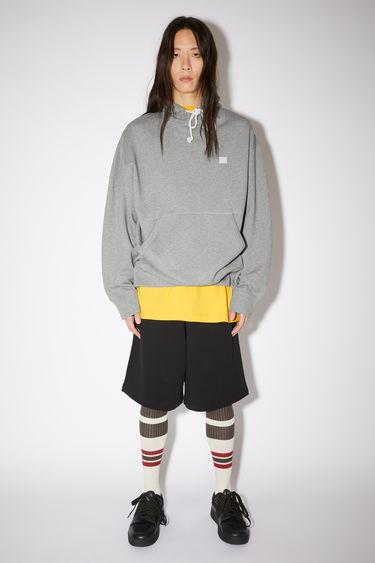 Acne Studios light grey melange oversized hooded sweatshirt is made of organic cotton with a face patch and ribbed details.