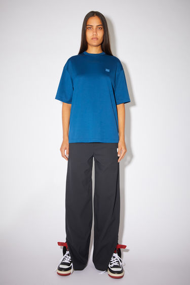 Acne Studios teal blue relaxed fit t-shirt is made of organic cotton with a ribbed crew neck and face logo patch.