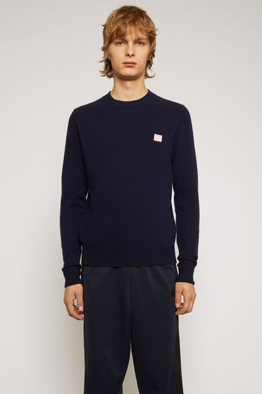 Acne Studios navy/pink sweater is knitted in a fine gauge from soft wool yarns and accented with a tonal face-embroidered patch on the chest.