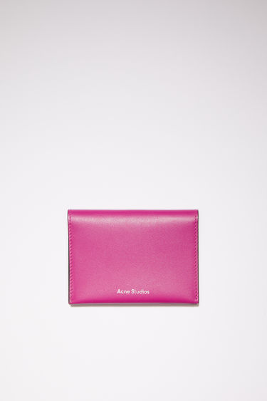 Acne Studios fuchsia pink bifold card holder is made of soft grained leather with four card slots and a silver stamped logo on the front.