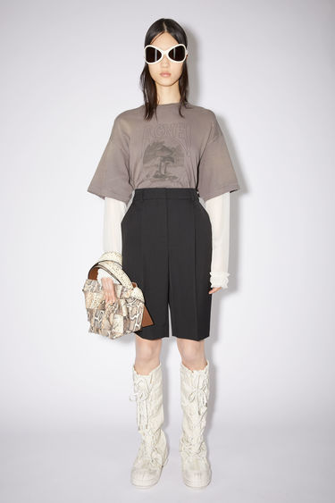 Acne Studios black shorts are tailored with a high-rise waist stitched with pleats and lead loosely into straight legs.