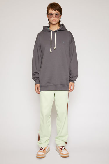 Acne Studios stone grey hooded sweatshirt is crafted from midweight loopback fleece to an oversized fit and finished with a tonal face patch on the chest.
