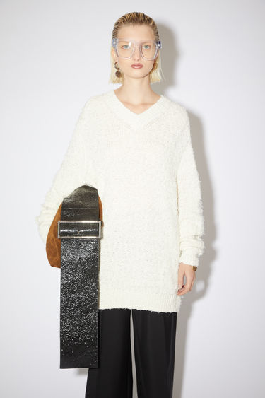 Acne Studios white feathery v-neck sweater is made of a cotton blend with a long, relaxed fit.