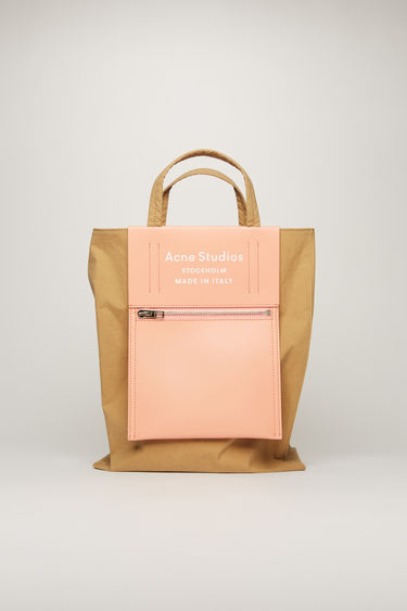 Acne Studios Baker Out M brown/pink is a medium-sized tote bag with an embossed logo pocket placed outside of the bag.