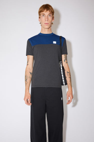 Acne Studios black colour block t-shirt is made of lightweight technical jersey with a reflective face logo at the chest.