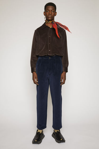 Acne Studios navy corduroy trousers are cut to a carrot-leg fit with single front pleats and finished with wide belt loops and back patch pockets.
