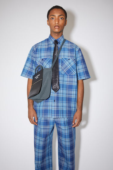 Acne Studios blue/navy short sleeve plaid shirt is made of a cotton blend with two chest pockets.