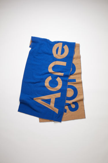 Acne Studios blue/beige oversized scarf is made of a soft recycled wool blend featuring bold, contrasting logo lettering on both sides.