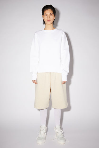 Acne Studios optic white regular fit crew neck sweatshirt features ribbed details and a face patch on the front.