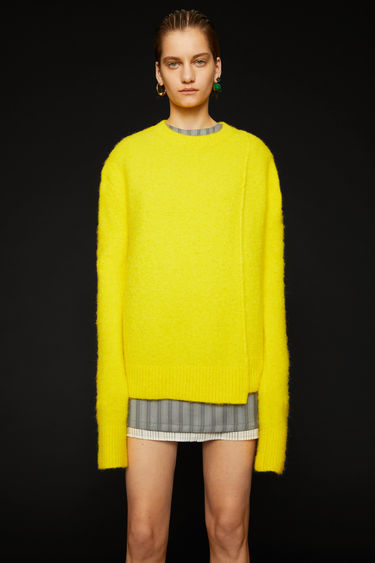 Acne Studios canary yellow sweater is crafted from an alpaca blend with hints of wool for a soft hand feel. It's shaped with a crew neck and finished with a stepped hemline.