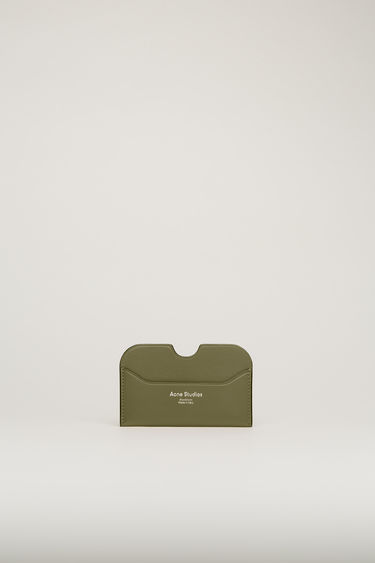 Acne Studios Elmas S dark green/black cardholder is crafted from soft grained leather with three card slots and accented with a cut-out at the midpoint of the central slot.