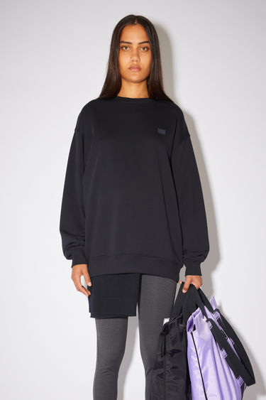 Acne Studios black oversized sweatshirt is made of organic cotton with a face logo patch and ribbed details.