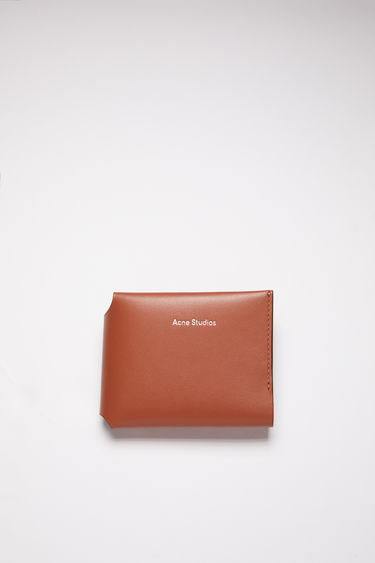 Acne Studios almond brown trifold card wallet is made of soft grained leather with a coin pocket, bill sleeve, and four card slots, featuring a silver stamped logo on the front.