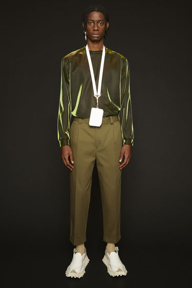 Acne Studios olive green cotton trousers are cut to tapered legs with a pleated front and finished with fixed turn-up hems.