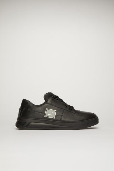 Acne Studios Steffey Lace Up Pl black/black take design cues from 80's tennis shoes. They're crafted from calf leather to a round-toe shape with a lace-up front and a rubber midsole and accented with a metal plaque that depicts a face motif in black.