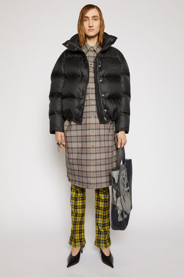 Acne Studios black down jacket is padded with recycled down and feathers and is shaped to a cocoon silhouette with binding running along the edges. The funnel collar has a packaway hood and accented with a tonal logo print at the chest.