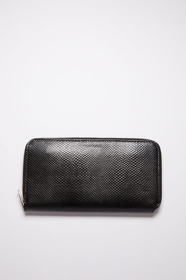 Acne Studios black continental wallet is made of calf leather with 12 card slots, two bill sleeves, and a zippered compartment for coins.