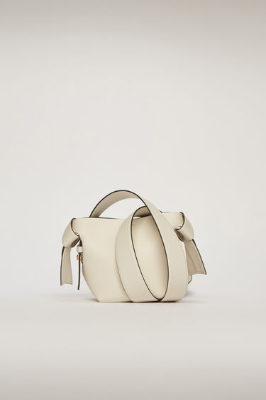 Acne Studios Musubi Micro white/black bag features knotted details inspired by the traditional Japanese obi sash. It's crafted from soft grain leather and comes equipped with a detachable shoulder strap and a top handle.