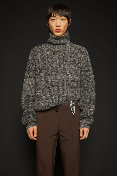Acne Studios black/white melange sweater is knitted from thick wool yarn to a ribbed design and shaped with a roll neck and raglan sleeves.