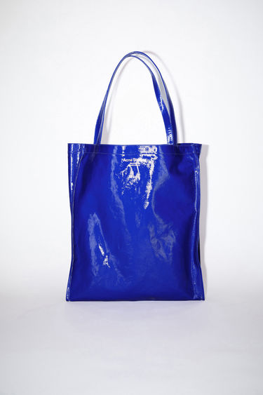 Acne Studios blue oilcloth tote bag features Acne Studios branding.