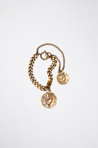 Acne Studios antique gold charm bracelet features two branded coins on fine and thick chains.