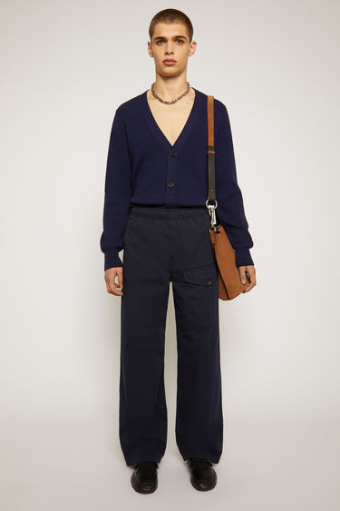 Acne Studios navy trousers are made from cotton that's garment-dyed to create light fading at the seams. They're cut in a straight shape that drapes loosely over the leg and finished with an elasticated drawstring waistband and a utilitarian flap pocket.