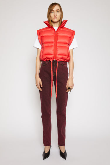 Acne Studios red quilted gilet is crafted from recycled down and feather-filled shell that is shaped with a high neck and drawstring hem. The front has zip pockets and a logo printed across the chest.
