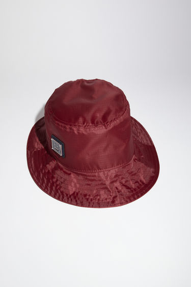Acne Studios burgundy bucket hat is made from technical ripstop and features a polished metal logo plaque with a face motif in black.