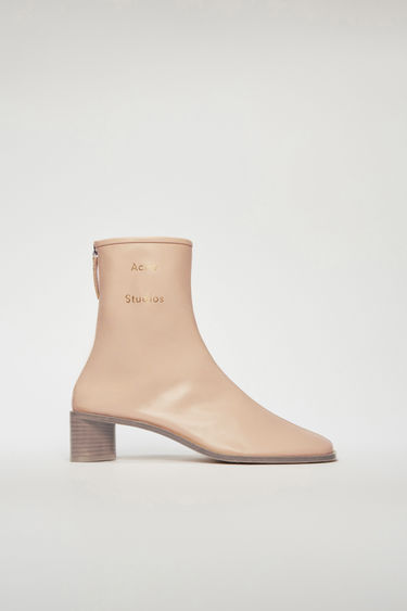 Acne Studios ecru beige boots are crafted to a slim silhouette from supple leather and set on a stacked block heel. They are accented with a silver-tone metal zip and a stamped logo on the ankle.