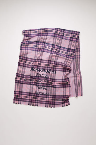 Acne Studios lilac/purple scarf is crafted to a wide dimension from soft wool that's woven with tartan checks and features a large-scale logo and care instruction print on front.